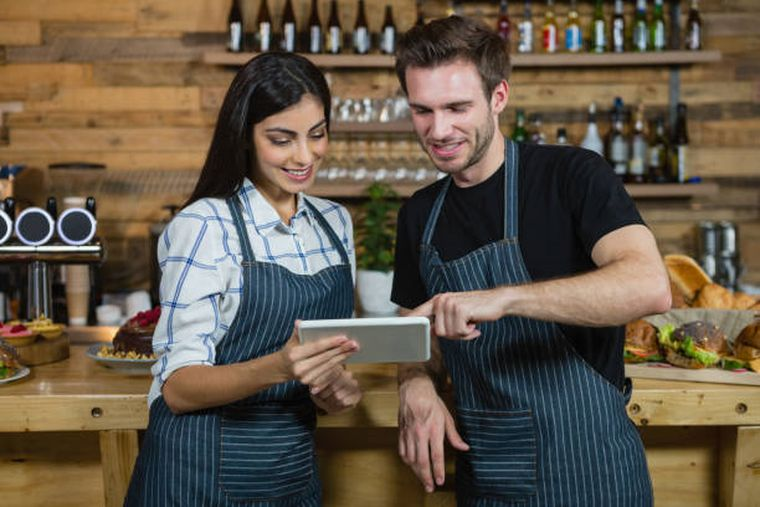 waiter-and-waitresses-using-digital-tablet-at-counter